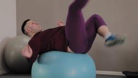 Gros trains gais d'homme sur la boule de forme physique banque de vidéos