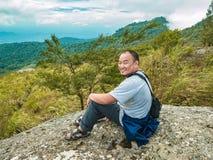 Gros Trekker asiatique se reposer sur la pierre à la montagne de Khao Luang en parc national de Ramkhamhaeng images libres de droits