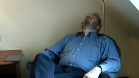 Gros type détendant sur un divan confortable banque de vidéos