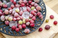 Groseille à maquereau surgelée avec des morceaux de glace d'un plat de vintage Photographie stock libre de droits