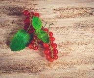 Groseille rouge mûre avec des feuilles sur un fond en bois images libres de droits