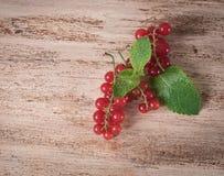 Groseille rouge mûre avec des feuilles sur un fond en bois photographie stock