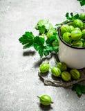Groseilles à maquereau et feuilles dans une tasse Sur la table en pierre Images libres de droits