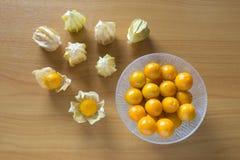 Grosellas espinosas anaranjadas en cuenco y en las tablas Fotografía de archivo