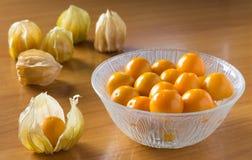 Grosellas espinosas anaranjadas en cuenco y en las tablas Foto de archivo