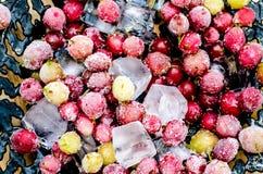 Grosellas espinosas congeladas con los cubos de hielo Foto de archivo libre de regalías