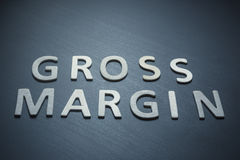 Gross margin written with wooden letters on a blue background Royalty Free Stock Photography