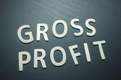 Gross profit written with wooden letters on a green background. To understand a concept of economics and finance stock photography