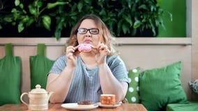 Grosse femme de sourire heureuse appréciant mâchant le beignet appétissant savoureux regardant la caméra banque de vidéos