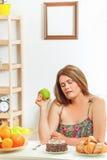 Grosse femme s'asseyant à la maison de table Photographie stock
