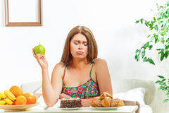 Grosse femme s'asseyant à la maison de table Image libre de droits