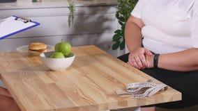 Grosse femme signant un contrat avec un nutritionniste photographie stock