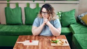 Grosse femme suivante un régime réfléchie choisissant entre les aliments de préparation rapide américains et le légume organique  banque de vidéos