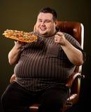 Grosse pizza mangeuse d'hommes d'aliments de préparation rapide Petit déjeuner pour la personne de poids excessif Photographie stock