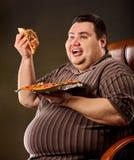 Grosse pizza mangeuse d'hommes d'aliments de préparation rapide Petit déjeuner pour la personne de poids excessif Image libre de droits