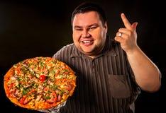 Grosse pizza mangeuse d'hommes d'aliments de préparation rapide Petit déjeuner pour la personne de poids excessif Images libres de droits