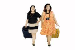 Grosses femmes marchant avec la valise Photographie stock