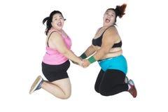 Grosses femmes sautant ensemble Photographie stock