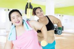 Grosses haltères d'ascenseur de femmes au centre de fitness Images stock