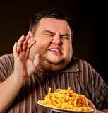 Grosses pommes frites mangeuses d'hommes d'aliments de préparation rapide pour la personne de poids excessif Image libre de droits