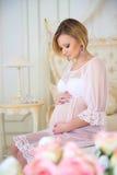 Grossesse et bébé de attente Mère enceinte s'asseyant sur un lit des roses Photographie stock libre de droits