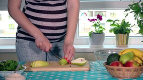 Grossesse et nutrition saine Le ventre et les mains de femme enceinte coupent en tranches le fruit de poire banque de vidéos