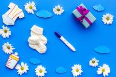 Grossesse et préparation pour l'accouchement Essai de grossesse près des fleurs sur la vue supérieure de fond bleu Photo libre de droits