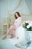 Grossesse, repos, les gens et concept d'attente - femme enceinte heureuse s'asseyant sur le lit et touchant son ventre à la maiso Photographie stock
