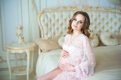 Grossesse, repos, les gens et concept d'attente - femme enceinte heureuse s'asseyant sur le lit et touchant son ventre à la maiso Photo libre de droits
