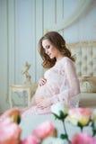 Grossesse, repos, les gens et concept d'attente - femme enceinte heureuse s'asseyant sur le lit et touchant son ventre à la maiso Photographie stock libre de droits