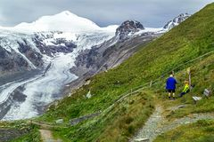 Grossglockner, Austria – July 27, 2017: People enjoying amazing view of glacier Grossglockner with snowy mountain peaks. Royalty Free Stock Image