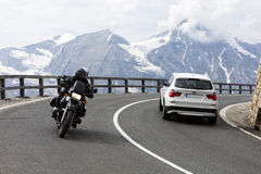 Grossglockner, Austria, 23 July 2015: Alpine road, motorbike and car speeding, Eastern Alps Stock Photos