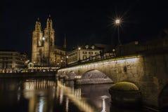Grossmunster教会和苏黎世街市在晚上 免版税库存照片