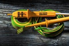 Grosso pezzo elettrico del tester di nastro rotolato degli elettricisti del cavo su di legno immagine stock libera da diritti