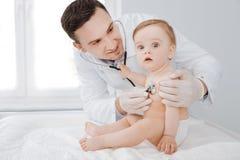Grote arts die zijn aanbiddelijke patiënt ervoor zorgen die gezond zijn Royalty-vrije Stock Foto's