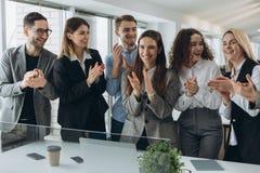 Grote baan! Het succesvolle commerci?le team slaat hun indient modern werkstation, vierend de prestaties van nieuw product stock foto's