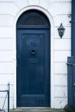 Grote blauwe houten deur met een tredendeel van een huis Stock Afbeeldingen