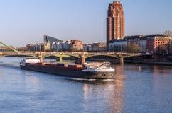 Grote boot onder de brug bij zonsondergang stock fotografie