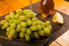 grote borstel van groene druiven in een ceramische plaat, een karaf en een glas van wijn en kaas stock afbeeldingen