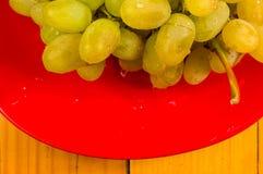 Grote borstel van groene druiven in een rode ceramische plaat op een houten achtergrond stock foto's