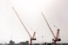Grote bouwwerf met inbegrip van verscheidene kranen die aan een complex gebouw werken Stock Fotografie