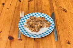 Grote braadschotel met eigengemaakte Apple-Kruimeltaartpastei wordt gevuld op een houten keukenvloer die stock foto