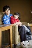 Grote broer die voor gehandicapte sibling geeft Stock Afbeelding