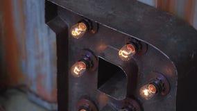 Grote bruine metaalbrief met verscheidene oranje bollampen opgezet aan het stock footage