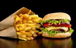 Grote cheeseburger met frieten op zwarte raad Stock Foto's