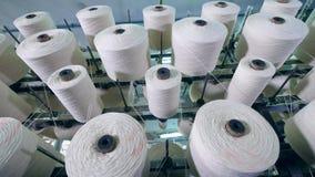 Grote die spoelen automatisch op een modern materiaal bij een textielinstallatie worden gespoeld stock videobeelden