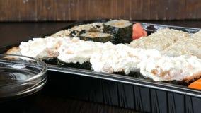 Grote die sushi met een verscheidenheid van sushibroodjes evenals maki, nigiri worden geplaatst, gunkan op een modieuze zwarte ac stock footage