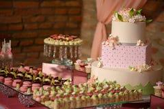 Grote die tiered cake drie met van de fluweelsuikerglazuur en suiker bloemen wordt opgesmukt, door een verscheidenheid van beet-g stock fotografie