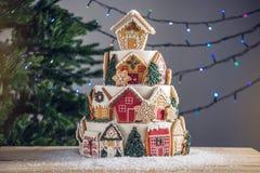 Grote die tiered Kerstmiscake met peperkoekkoekjes wordt verfraaid en een huis op bovenkant Boom en slingers op de achtergrond stock foto's