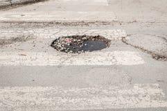 Grote diepe gevaarlijke pathole in het midden van de asfaltweg, gevaar voor auto's het drijven kan een ongeval of een analyse van royalty-vrije stock afbeeldingen